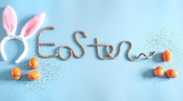 Iscrizione creativa di pasqua sull'azzurro con elementi di decorazioni pasquali.