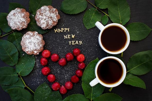 Iscrizione del nuovo anno su un bordo nero con cupcake