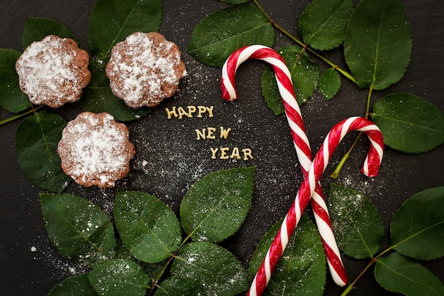 Iscrizione del nuovo anno su un bordo nero con cupcakes e caramelle rosse