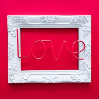 Iscrizione di amore con cornice sul tavolo rosso