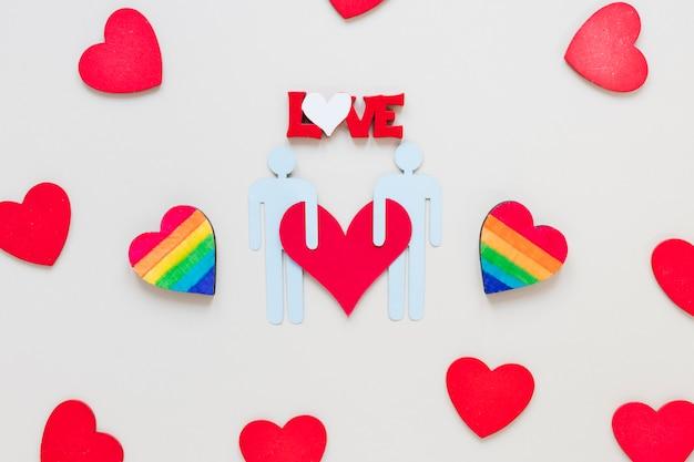 Iscrizione di amore con cuori arcobaleno e icona di coppia gay