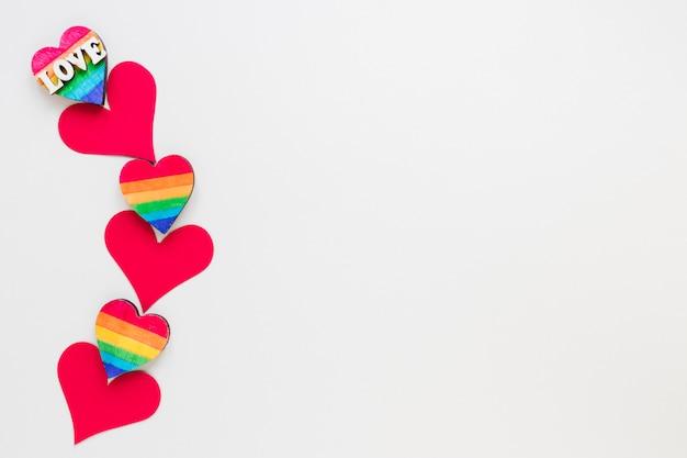 Iscrizione di amore con piccoli cuori rossi di carta e arcobaleno