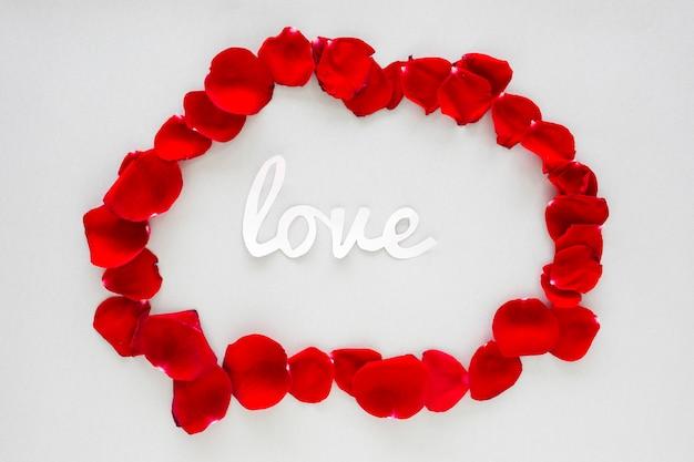 Iscrizione di amore di carta con petali di rosa sul tavolo grigio
