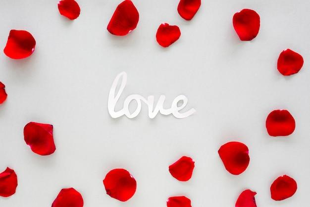 Iscrizione di amore di carta con petali di rosa sul tavolo