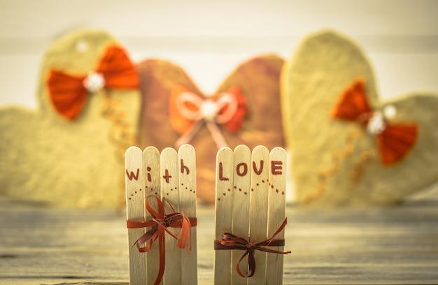 Iscrizione di amore di san valentino su piccoli bastoncini di legno con un cuore