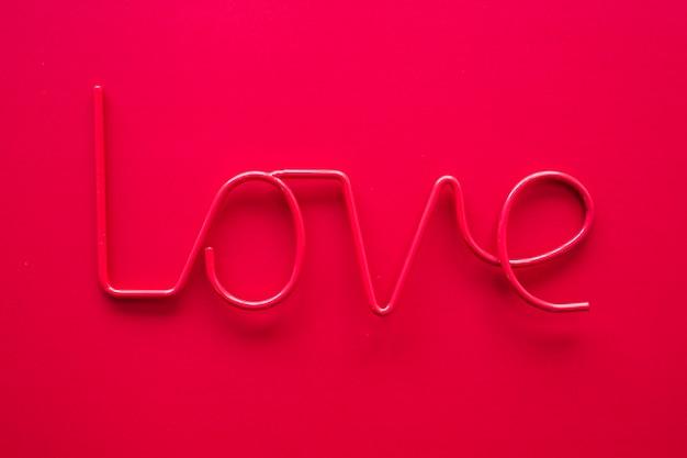Iscrizione di amore rosa sul tavolo rosso