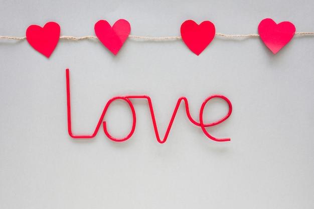 Iscrizione di amore rosso con cuori di carta sul tavolo