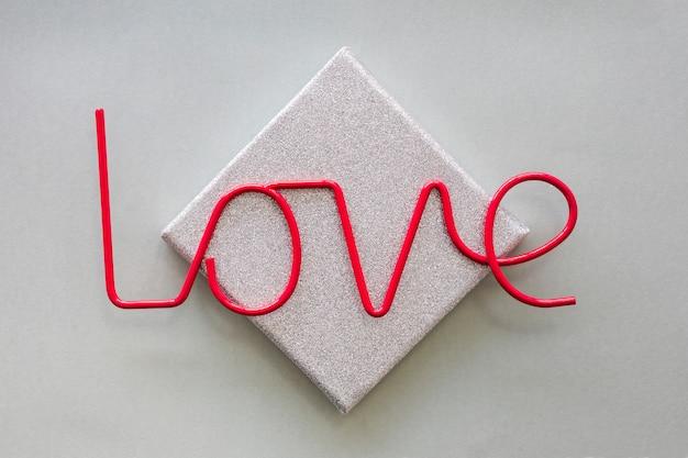 Iscrizione di amore rosso sulla scatola grigia