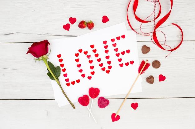 Iscrizione di amore su carta vicino a cuori di cioccolato, nastro e fiori