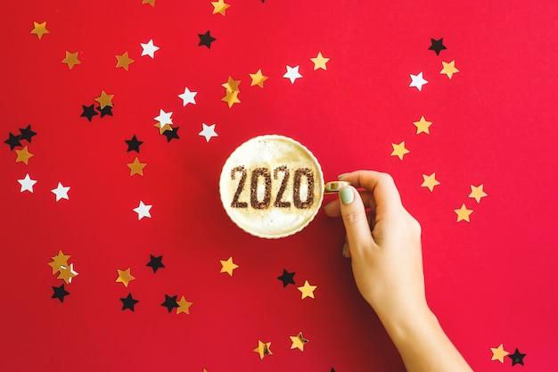Iscrizione di concetto di 2020 anni su una tazza di cappuccino su rosso.