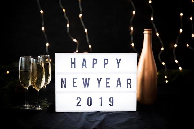 Iscrizione di felice anno nuovo 2019 a bordo con bottiglia