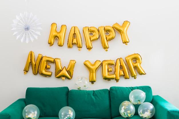 Iscrizione di felice anno nuovo da palloncini gialli