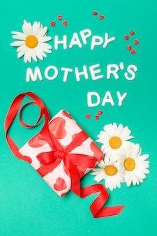 Iscrizione di giorno di madri felice vicino a fiori bianchi e scatola regalo