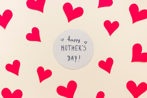 Iscrizione di happy mothers day con cuori di carta sul tavolo