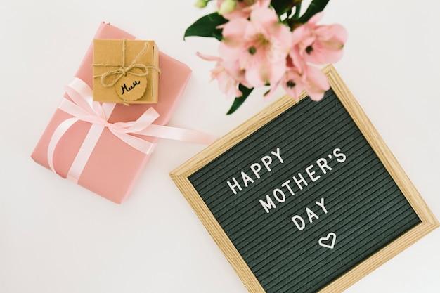 Iscrizione di happy mothers day con fiori e regali