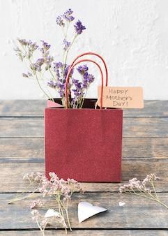 Iscrizione di happy mothers day con fiori in sacchetto di carta
