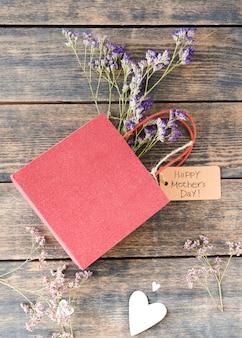 Iscrizione di happy mothers day con fiori in un piccolo sacchetto di carta