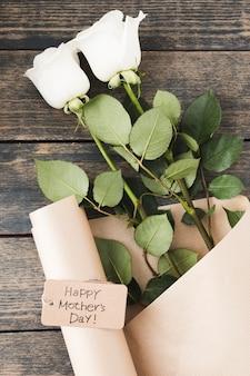 Iscrizione di happy mothers day con rose bianche sul tavolo