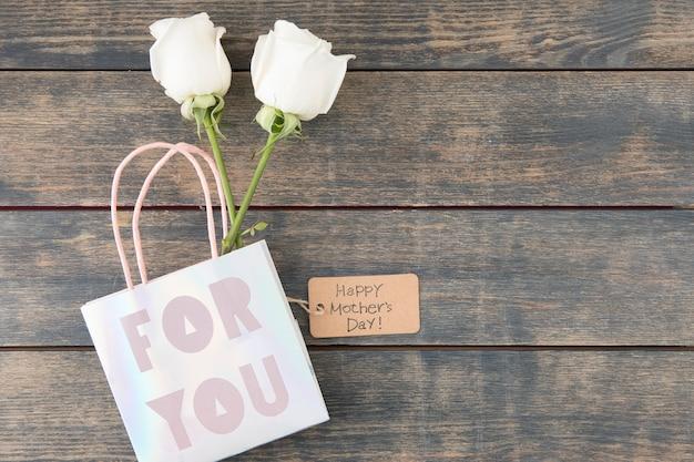 Iscrizione di happy mothers day con rose in sacchetto di carta