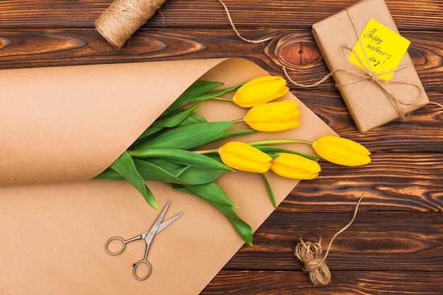 Iscrizione di happy mothers day con tulipani e regalo