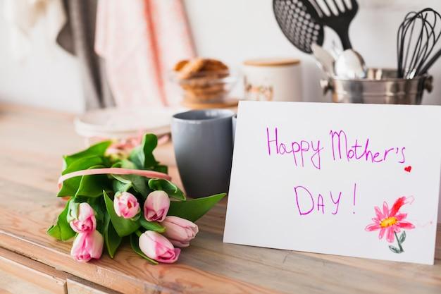 Iscrizione di happy mothers day con tulipani sul tavolo