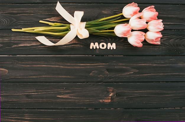 Iscrizione di mamma con bouquet di tulipani sul tavolo scuro