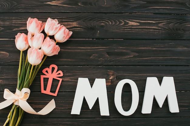 Iscrizione di mamma con bouquet di tulipani sul tavolo