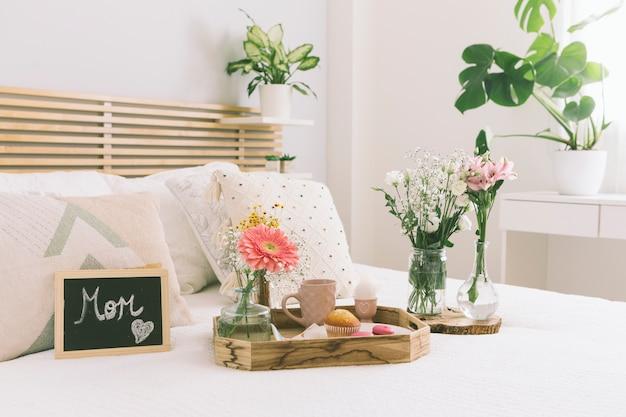 Iscrizione di mamma con fiori e dolci sul vassoio