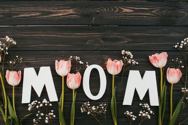 Iscrizione di mamma con tulipani sul tavolo di legno scuro