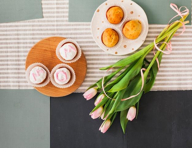 Iscrizione di mamma su cupcakes con fiori di tulipano