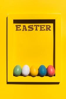 Iscrizione di pasqua nel telaio con uova colorate