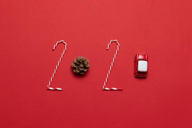 Iscrizione di vacanza 2020 di natale e capodanno da vari oggetti decorati classica palla di bagattelle di vetro rosso, macchinina su sfondo rosso. bordo orizzontale.