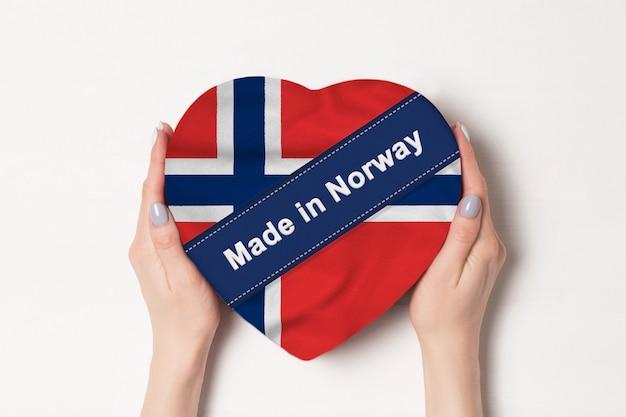 Iscrizione fatta in norvegia la bandiera della norvegia. mani femminili che tengono una scatola a forma di cuore. .