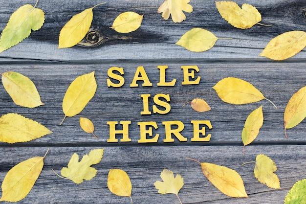 Iscrizione gialla la vendita è qui. cornice di foglie gialle