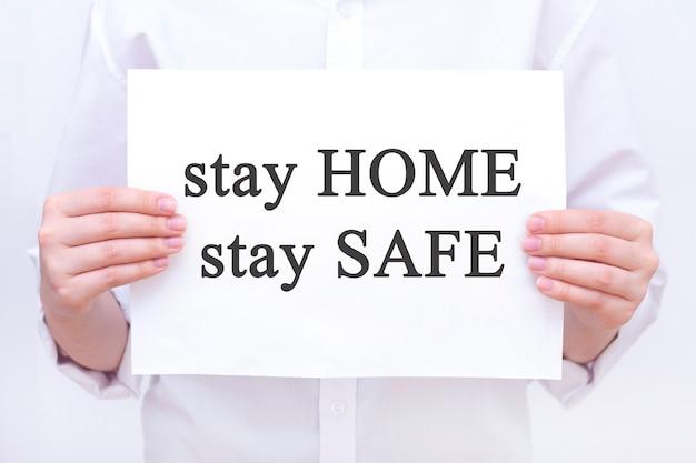 Iscrizione resta a casa. su un pezzo di carta nelle mani di un uomo, un dottore. coronavirus, pandemia, resta a casa, resta al sicuro