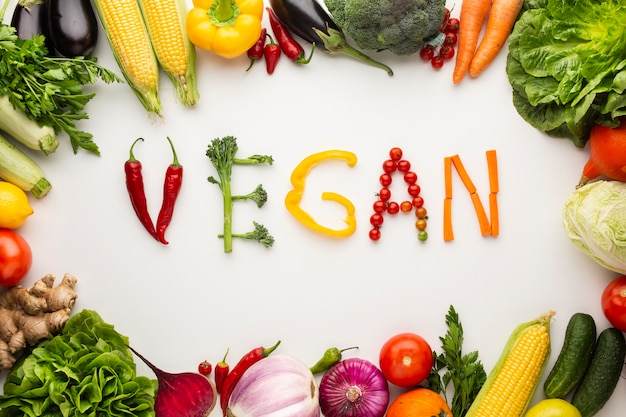 Iscrizione vegana vista dall'alto fatta di verdure su sfondo bianco