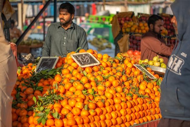 Islamabad, territorio della capitale islamabad, pakistan - 3 febbraio 2020, un venditore sta aspettando che i clienti nel mercato ortofrutticolo vendano frutta arancione.