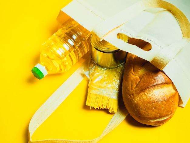 Isolamento delle scorte alimentari di crisi degli approvvigionamenti alimentari sulla superficie gialla. vermicelli, pasta, conserve, banane, burro, pane.