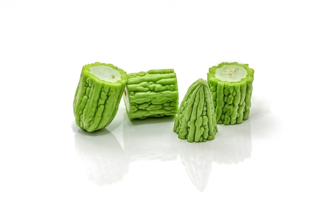 Isolato della zucca amara verde affettata sul bianco