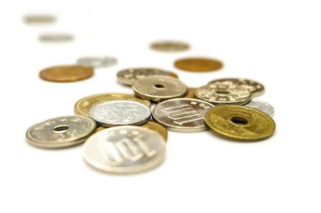 Isolato di diffusione delle monete di valuta di yen del giappone su bianco.