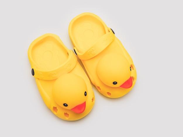 Isolato giallo delle scarpe dell'anatra del bambino su fondo bianco
