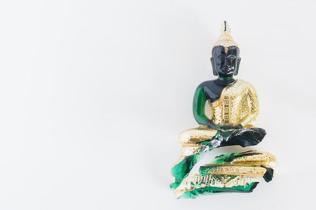 Isolato rotto della statua di emerald buddha su fondo bianco
