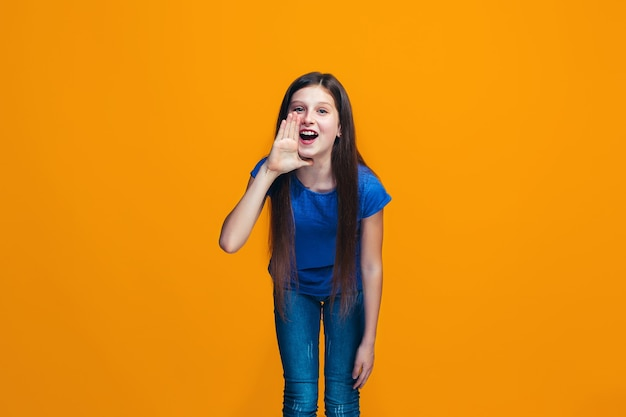 Isolato su giallo giovane ragazza adolescente casuale che grida allo studio