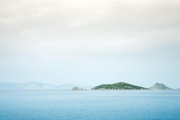 Isole nebbiose della montagna nebbiosa coperte di nebbia, paesaggio del lago del mare calmo