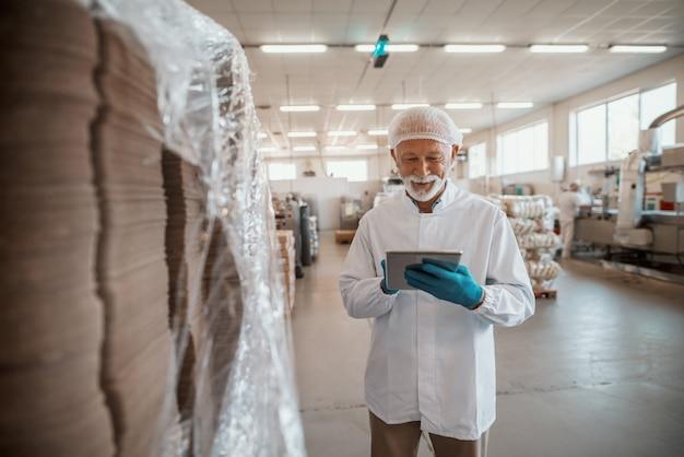 Ispettore adulto senior caucasico sorridente vestito in uniforme bianca facendo uso della compressa per la valutazione di qualità del cibo nella pianta alimentare.