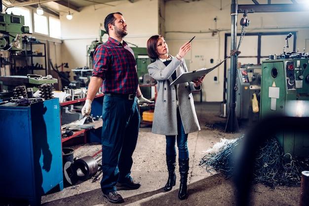 Ispettore di sicurezza femminile che parla con il macchinista alla fabbrica