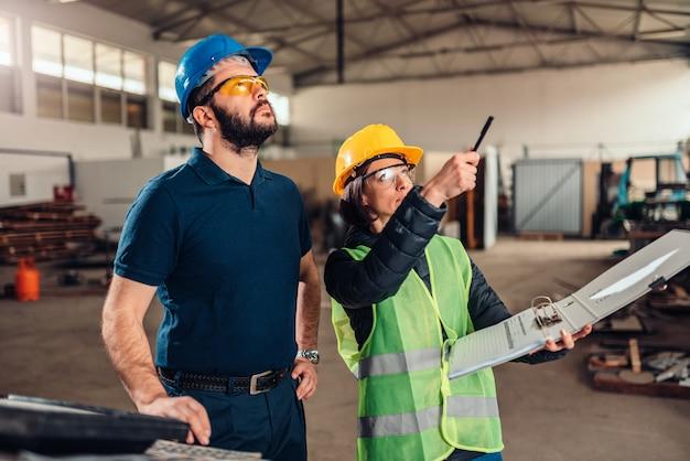 Ispettore di sicurezza sul posto di lavoro che scrive un rapporto alla fabbrica industriale