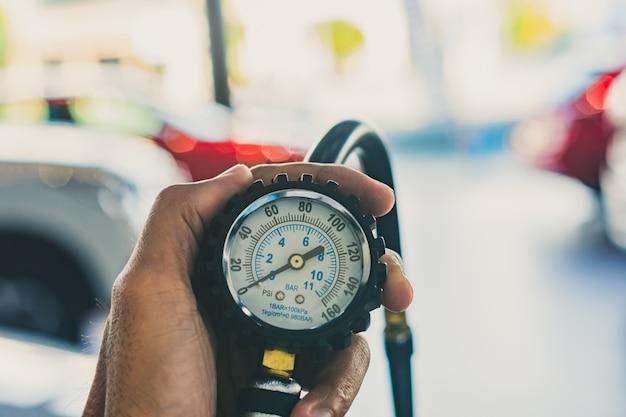 Ispezione auto uomo asiatico misura quantità gomme di gomma gonfiate auto.