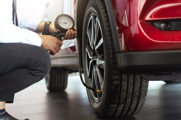 Ispezione auto uomo asiatico misura quantità gonfiaggio auto pneumatici in gomma.chiudi mano che tiene la macchina manometro gonfiato per la misurazione della pressione dei pneumatici auto per automotive, immagine di automobili