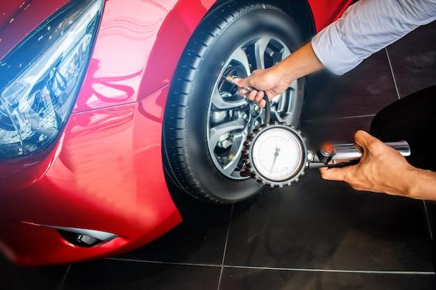 Ispezione dell'auto da uomo asiatico misura della quantità gomme di gomma gonfiate
